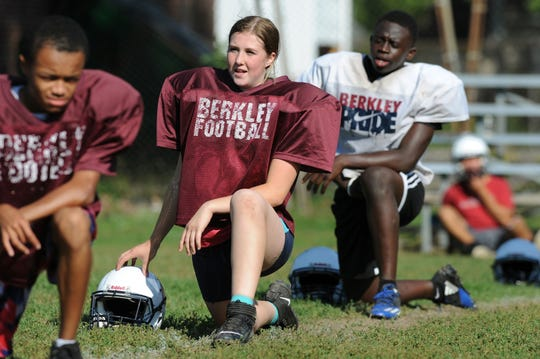 Berkley High School student Marcella DePaul,  who plays safety on the team's varsity football team, stretches with her teammates during a recent practice.