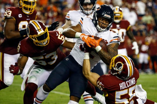 Chicago Bears running back David Montgomery (32) is dragged down by Washington linebacker Cole Holcomb (55) with help from linebacker Jon Bostic (53) during the second half on Monday.