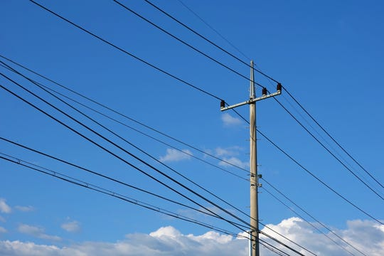 Electric pole with blue sky and clouds.