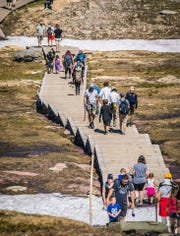 Visitors of all ages traverse the boardwalk at Logan Pass