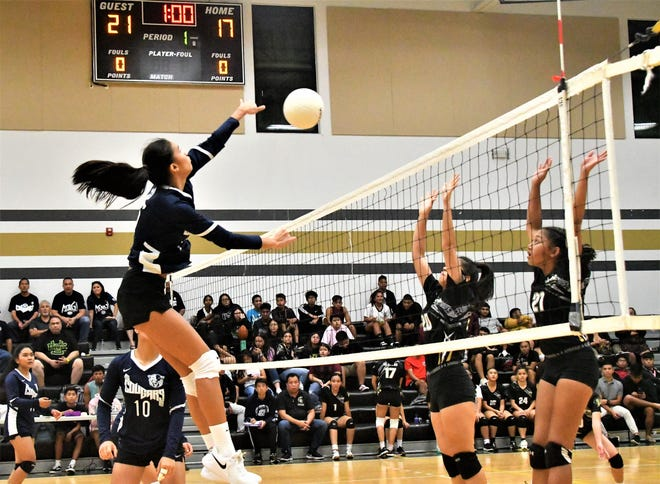 Academy Cougars' Kristen Serrano, left, cuts a shot against the Tiyan Lady Titans in their IIAAG High School Girls Volleyball match Sept. 24 at Tiyan High School. The Cougars won 3-1.