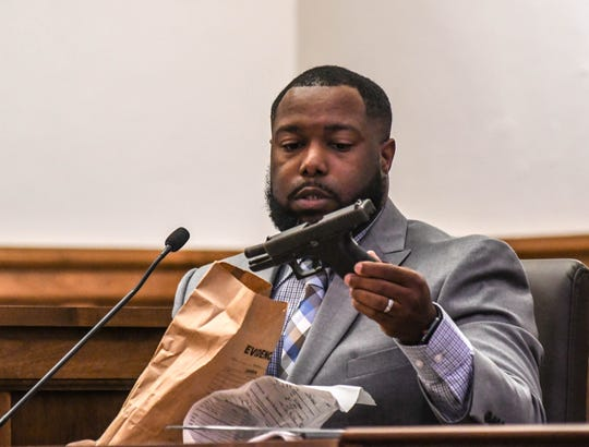 Special Agent Leo Clemons holds a handgun, evidence collected from the suspect's vehicle, during Victor Mitchell's trial Sept. 24, 2019.