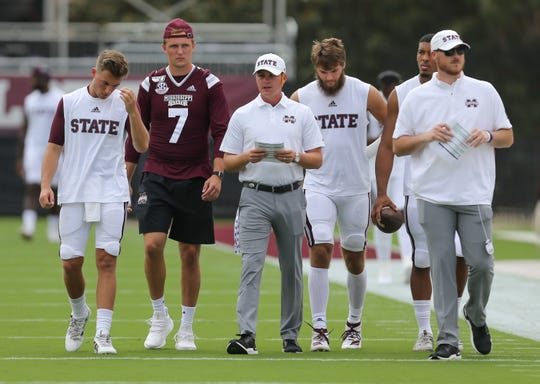 Mississippi State quarterbacks coach Andrew Breiner (center) leads the Bulldog quarterbacks out for warm-ups before last week's game against Kentucky.