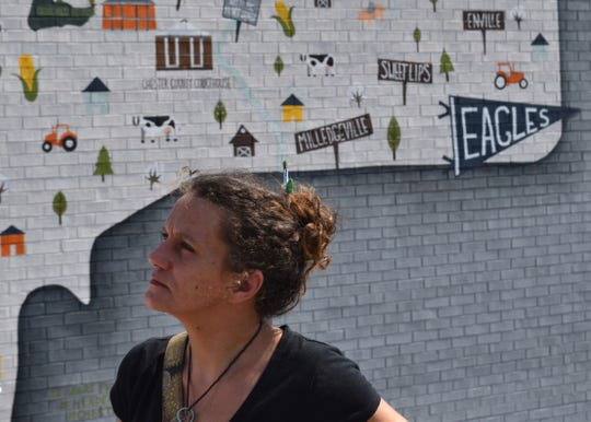 Mural artist Loralea Landrum stands in front of her latest work, which depicts a map of Chester County on the Bramblett Group building on Main Street in downtown Henderson, Tenn., on Sept. 19, 2019.