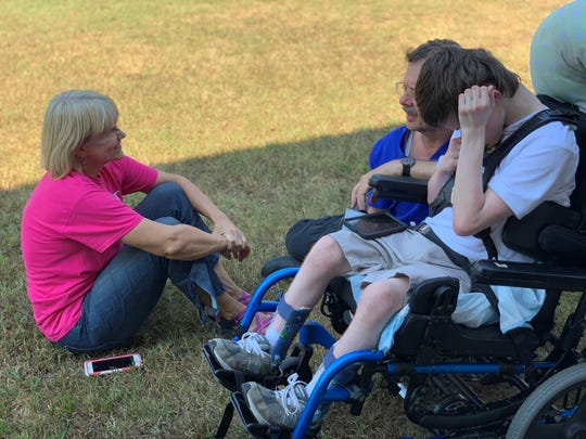 Kathy Southall, the secretary at Sacred Heart of Jesus High School, sits with a student during Champion's Day, an annual event for Jackson-Madison County and surrounding area students with special needs to enjoy a day of fun, games and activities at the Jackson Fairgrounds.
