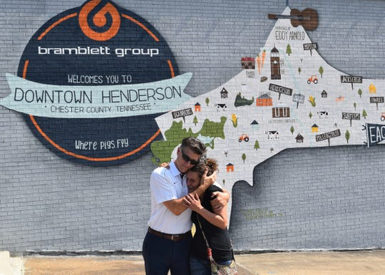 Area Relief Ministries Executive Director Mike Roby hugs mural artist Loralea Landrum in front of her latest mural depicting Chester County on Main Street in downtown Henderson, Tenn. on Sept. 19, 2019.