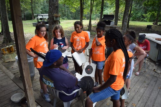 Campers at the Kops and Kids Adventure Program, a free camp put on by the St. Landry Sheriff's Office, listen intently to camp counselor Ron Rideau as he explains how to properly hold a gun.