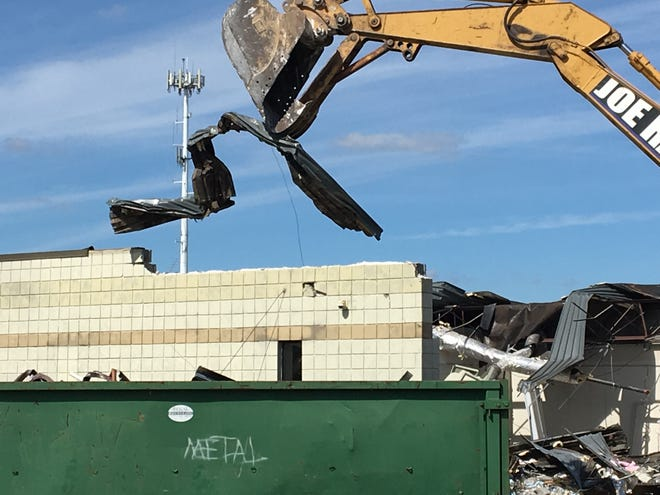 An excavator from Fowlerville-based Joe Raica Excavating carries a piece of metal to put into a dumpster on Tuesday, Sept. 24, 2019 during the process of demolishing the county's former 911 Central Dispatch building.