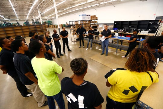 Operations Manager John Allen leads a morning meeting with employees at Material Bank, a conduit for architects and designers to preview samples for projects, at the Memphis facility Sept. 24, 2019.