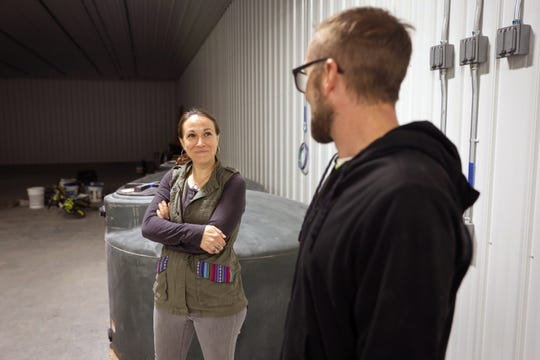Abbie Testaberg smiles at her husband Jody on April 18 in what will become one of their hemp grow rooms in River Falls, Wisconsin. Right now, the room serves as a space for their two sons to ride bikes. Testaberg says she hopes if Wisconsin legalizes marijuana, it would ensure that large companies do not dominate the market.