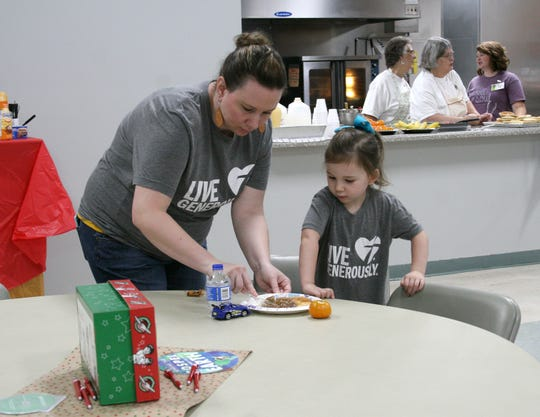 "Monique Lawrence (left) cuts up pancakes and sausage for her daughter, Moriah Lawrence, at Saturday's pancake breakfast at Eastside Baptist Church. The breakfast was provided by Lawrence's husband, Brandon, of Thrivent Financial to kick off the North Central Arkansas Operation Christmas Child program. Representatives from churches around the Twin Lakes Area came to find out about the ""shoebox"" program."
