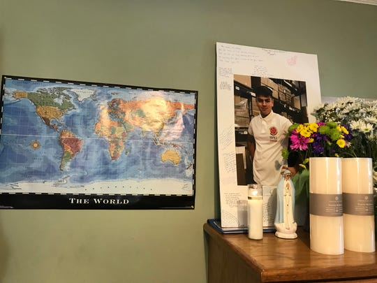 A world map hangs in Steven's room next to candles and photos in memory of his life.