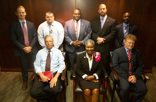 Back row, left to right, Sgt. Robbie Whitmore, Sgt. Greg Schnupp, Investigator Terrance James, Investigator Andrew Magnus, Investigator Antony Shannon stand behind Investigator Guy Naquin, Victim's service advocate Carolyn Tyus, and Prosecutor Damon Lewis.