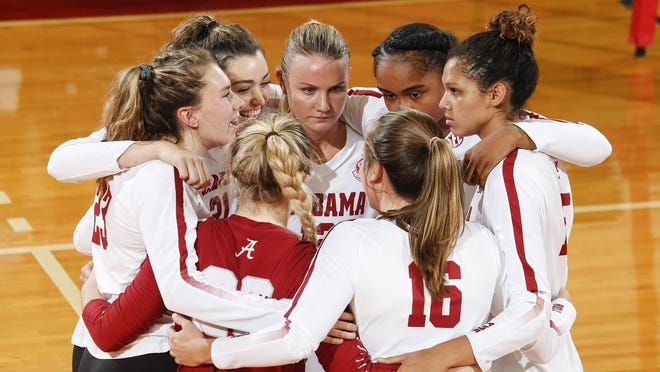 Members of the Alabama volleyball team huddle during a match, including Hayley McSparin (No. 23) and Ashley Homan (center).