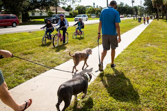 Bonita Springs Middle School students bike on the grass around Sarah Warfel, left, and Chester Warfel, right, as they walk their dogs Rita and Bruno on their way to pick up their niece from school on West Terry Street in Bonita Springs on Tuesday, September 24, 2019. The city of Bonita Springs plans to spend $4 million to complete a project replacing the sidewalk along the section of West Terry Street between U.S. 41 and Old 41 Road with a new multi-use path for pedestrians and bicyclists.