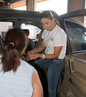 Luna County Parents As Teachers Certified Child Car Seat Technician Mirna Chaires, right, explains the proper installment of the car seat to a Deming parent.