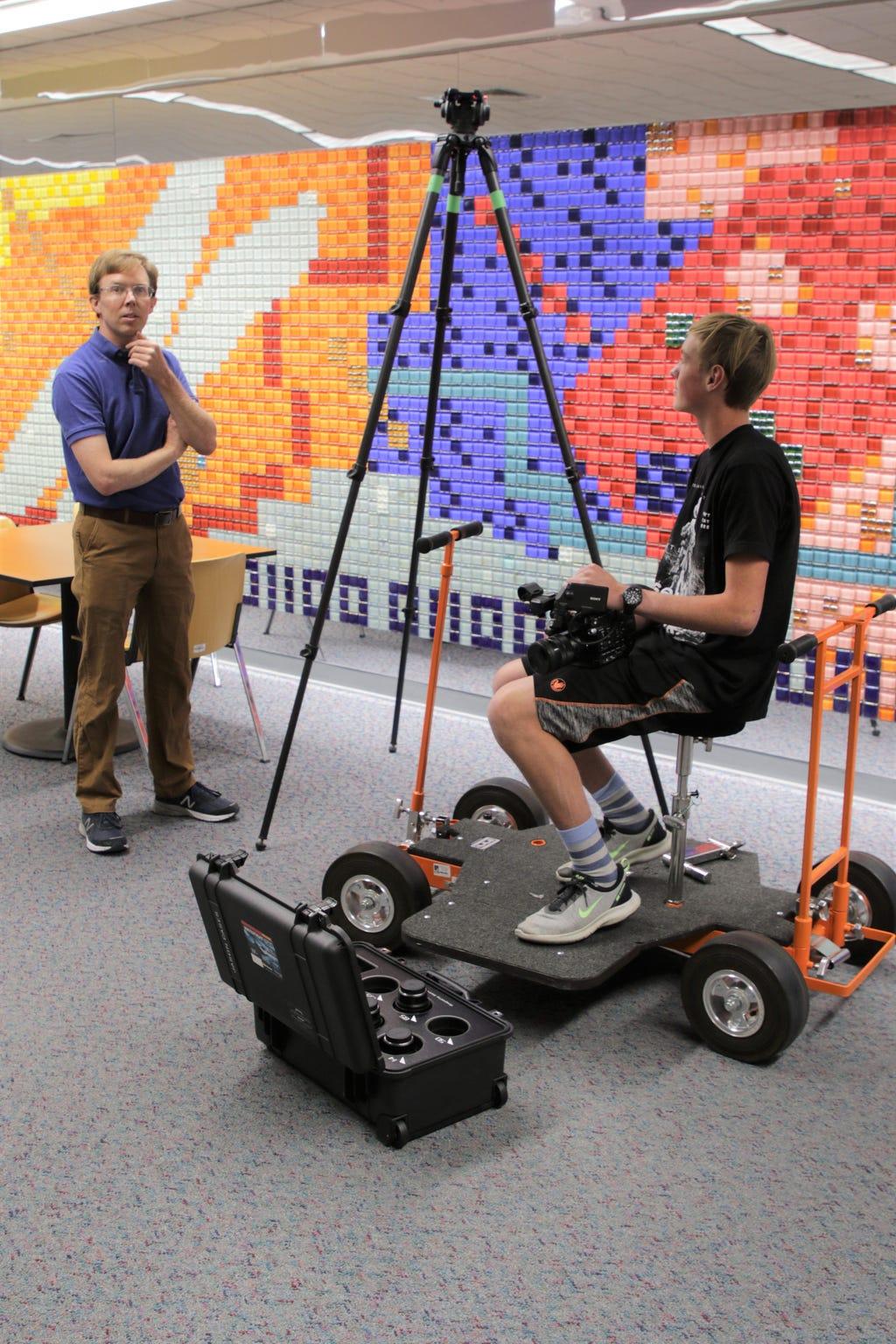 San Juan College professor Luke Renner, left, and student Carl Keller set up a camera tripod used by students in the digital arts program.