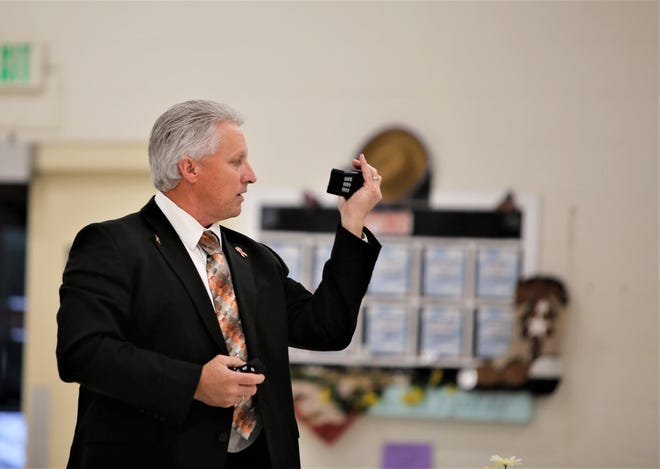 Aztec Municipal School District Superintendent Kirk Carpenter holds up a radio and says it saved lives during the Aztec High School shooting. Carpenter said the radio was purchased using mill funding, which will be on the ballot in November.
