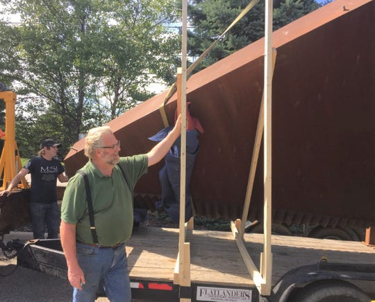 Sculptor Ken Thompson watches his piece of art getting prepped for transport.