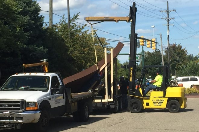 The massive steel sculpture that was damaged in Sunday's two-car crash was hauled away for repairs on Tuesday.