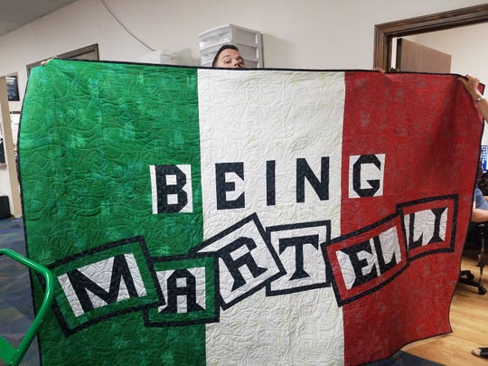 """David Martelli, a cast member of the reality show """"Being Martelli,"""" holds up a sign bearing the show's name."""