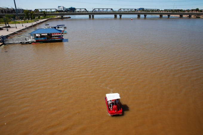 Visitors use a paddle boat in brown water at Tempe Town Lake on Sept. 24, 2019. Water releases from SRP into a normally dry Salt River has tinted the recreational lake brown.