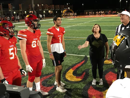 Executive Director of Teen Lifeline Michelle Moorhead tosses the game coin at Friday's Chaparral vs. Saguaro game. Jake Gustafson is the referee.