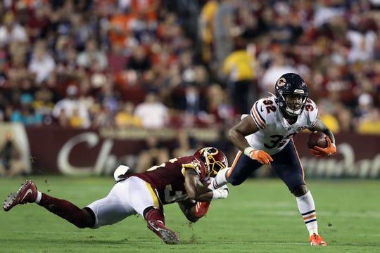 David Montgomery intenta eludir la marca del defensivo de Redskins.
