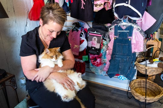 Spring Burrell, owner of Ufuri Pet Salon in Port Huron, holds Banjo, a 7-year-old cat that lives at the store Tuesday, Sept. 24, 2019.