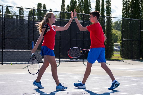 St. Clair freshman Hadley Schwarz, left, high-fives her brother Quinn after a point during a tennis match against Cranbrook Monday, Sept. 23, 2019, at St. Clair High School. The brother-sister duo are St. Clair's No. 1 ranked doubles team.