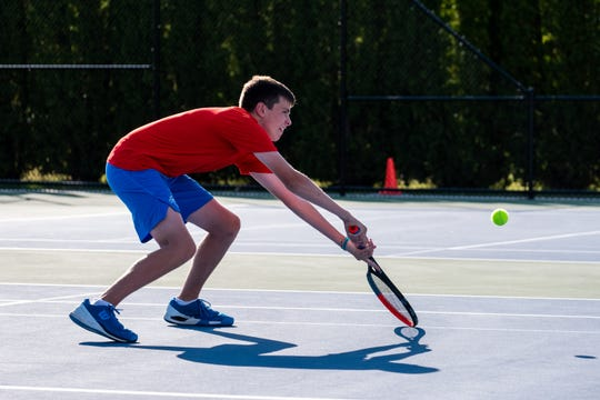 St. Clair junior Quinn Schwarz goes low to return the ball during a tennis match against Cranbrook Monday, Sept. 23, 2019, at St. Clair High School.