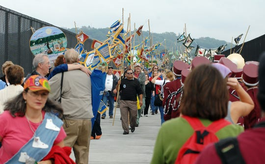 Volunteers and community members make their way over the Walkway Over the Hudson in a ceremonial east meets west parade on the deck on the bridge on Saturday, Oct. 3, 2009.