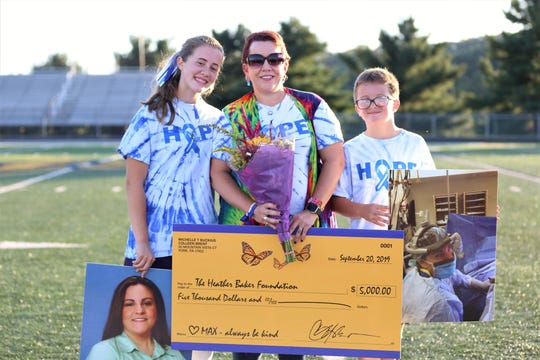Eastern York field hockey player Claire Rumsey poses with her mother, Heather Brent and her brother, Corban, prior to a game against Gettysburg last week. The two teams raised over $6,000 for the Heather Baker Foundation, including a $5,000 donation from Brent. Rumsey's stepmother and Brent wife, Michelle Buckius, died from colon cancer in August.