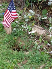 A groundhog hole by a grave site is one of many dotting the landscape of the cemetery.