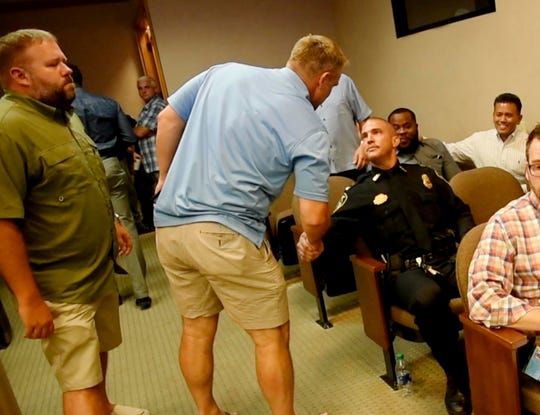 People go up to Ben Raymond during the city council meeting to congratulate him when he was unanimously voted as the city's next police chief.