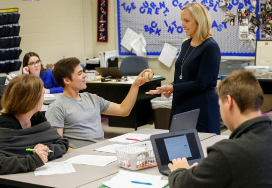 "Joe Hart, a senior at Fordland High School, hands a baseball to his teacher Melissa ""Misty"" Grandel during class. During high school, she has most students twice and some as many as five times."