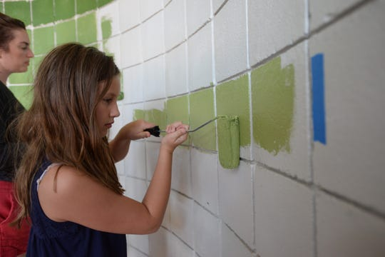 Madeleine Ely, 10, helps paint one of the lighter green rows of an ombre mural in a stairwell at Betton Place shopping center during the first event in Knight Creative Communities Institute's Placemaking Week that began Monday, Sept. 23, 2019.
