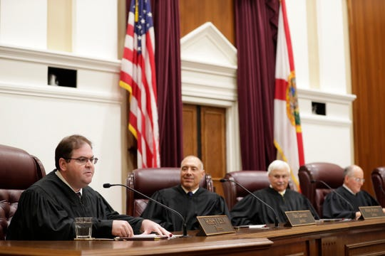 Newly enrobed Supreme Court Justice Robert Luck speaks from his new seat during an investiture ceremony held for Supreme Court Justices Carlos Muñiz and Luck at the Supreme Court of Florida Tuesday, Sept. 24, 2019.