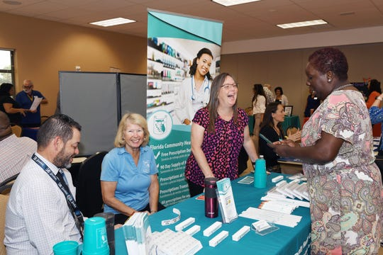 Roxy Brown of CareBag, right, talks with Florida Community Health's Raymond Correa, left, Irene Torreggiani and Robyn Connor at the 2019 COSA Showcase of Services.