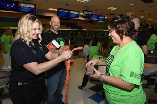 Brothers Big Sisters CEO Stacey Watson-Mesley, left, and Michael Mesley sell raffle tickets to Mandi Donayre of St. Lucie Elementary at the 2019 Bowl for Kids' Sake event in St. Lucie West.
