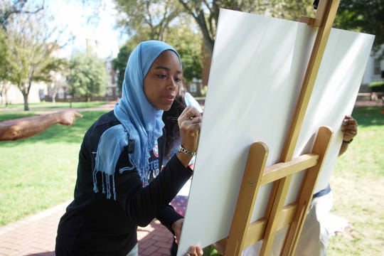 Madinah Wilson, with the Biden Institute, signs a poster on the Green at the University of Delaware on Tuesday during an event for National Voter Registration Day that got students visiting the Green to register to vote.