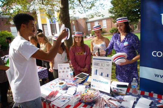 (left to right)Amani Thurman, 21, a senior at the University of Delaware, tries on a campaign hat that Lindsay Hoffman, a professor at University of Delaware gave him during an event Tuesday, Sept. 24, to get students to register to vote on National Voter Registration Day.