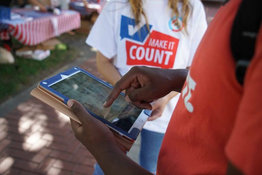Ahmid Mageid, 20, a junior at the University of Delaware uses an iPad to register to vote on National Voter Registration Day Tuesday, Sept. 24.