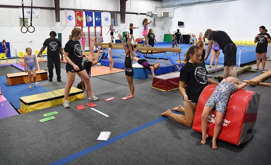 Coaches work with youngsters in the beginning gymnastics classes at Gymnastics Sport Center. The center also offers tumbling, GymKata, team gymnastics, parkour and birthday parties.