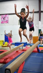 Young gymnasts practice their skills on the balance beam at Gymnastics Sport Center.
