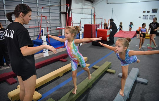 Gymnastics coach McKaylee Reese works with Emie Langley and Arabella Brooks, right, as they practice their arabesques on the beam at Gymnastics Sport Center.