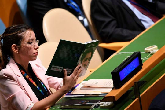 "A delegate from Venezuela holds up a book referring to Simon Bolivar, a Venezuelan military and political leader, titled ""Bolivar, Heroe, Genio y Pensamiento Universal"" (Bolivar, hero, genius and universal thinker), during US President Donald Trump's address at the 74th Session of the United Nations General Assembly at UN Headquarters in New York, September 24, 2019. (Photo by SAUL LOEB / AFP)"