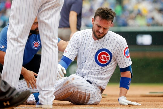 Chicago Cubs third baseman Kris Bryant (17) is tended to by medical staff after suffering an apparent injury while stepping on first base as he was forced out for a double play against the St. Louis Cardinals to end the third inning at Wrigley Field.