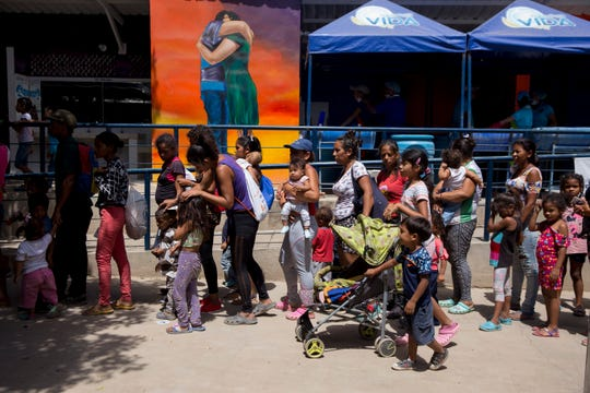 Families of Venezuelans wait in line for food in a migrant refuge on the Colombia-Venezuela border on September 11, 2019.