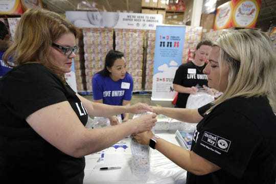 Heather Sorebo,  Jess Fraley and Robyn Harma repack diaper donations to support the Fox Cities Diaper Bank at the Valley Packaging Industry warehouse in Appleton on Wednesday.